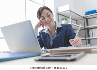 Smiling businesswoman working at office desk and writing down notes on a notebook