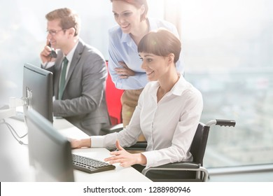 Smiling businesswomen discussing by colleague working at desk in modern office
