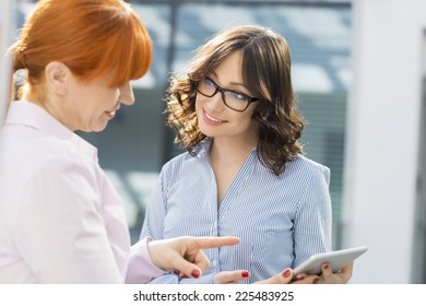 Smiling businesswomen discussing over tablet PC in office