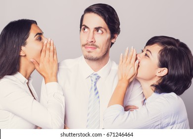 Smiling businesswomen whispering to male leader