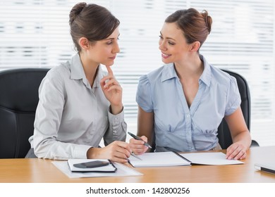 Smiling businesswomen working together on documents at desk in office