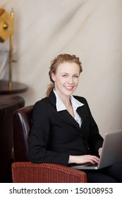 smiling busineswoman working on laptop in hotel