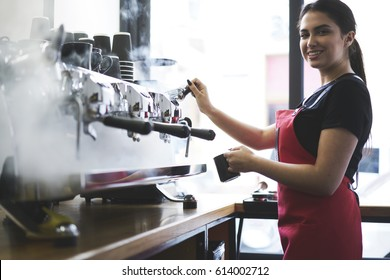 Smiling busty female barista using professional coffee machine enjoying job in cafe improving skills of making cappuccino, charming young trainee in uniform learning how to temperate drinks with steam