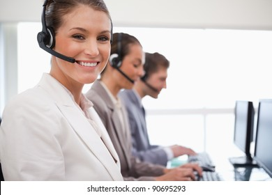 Smiling call center agent with working colleagues behind her