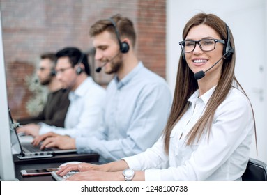 smiling call center employee sitting at his Desk