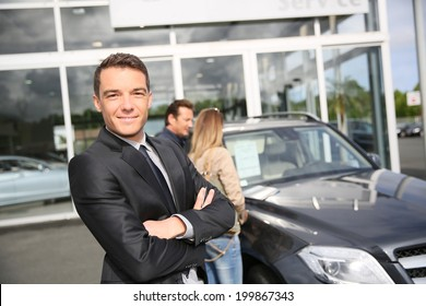 Smiling car dealer standing by vehicle, clients in background