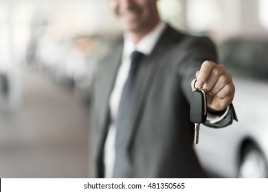 Smiling car salesman handing over your new car keys, dealership and sales concept