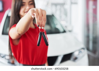 Smiling car salesman handing over your new car keys, dealership and sales concept. Happy girl the buyer.