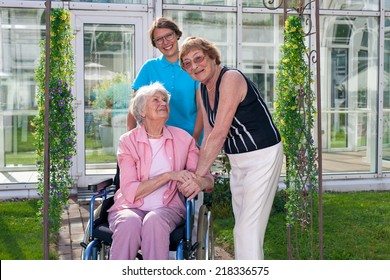Smiling Care Taker, Looking at Camera, for Old Age Patient on Wheel Chair, visited by an elderly lady. Captured at Grassy Green Garden with Glassy Home Care Building Background.
