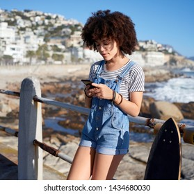Smiling carefree woman using her mobile cell phone by the ocean at sunset