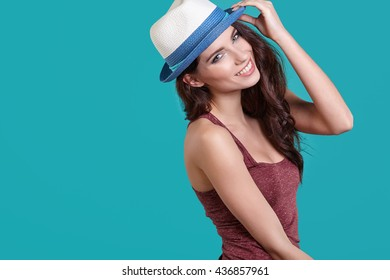Smiling carefree woman wearing white straw hat with hair motion on blue background