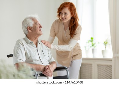 Smiling caregiver helping disabled senior man in a wheelchair