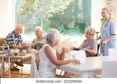 Smiling caregiver supporting happy elderly woman in the wheelchair in the nursing house