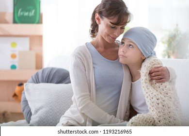 Smiling caregiver supporting sick child with cancer wearing blue headscarf