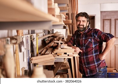 Smiling carpenter and small business owner, looking at the camera, while standing confidently in his workshop with shelves of wooden planks