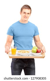 A smiling carrying a wooden tray with drinks and food isolated against white background