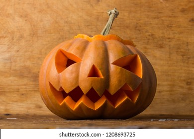 Smiling carved pumpkin on a rustic wood background
