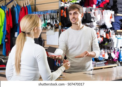 smiling cashier helping customer at the pay desk