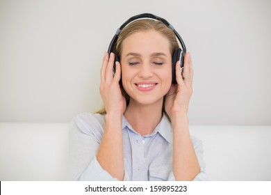 Smiling casual blonde listening to music with closed eyes in bright living room