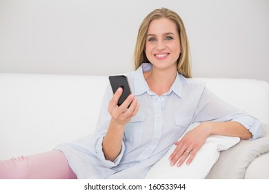 Smiling casual blonde relaxing on couch holding smartphone in bright living room