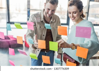 smiling casual businessman and businesswoman putting colorful sticky notes on glass window in office