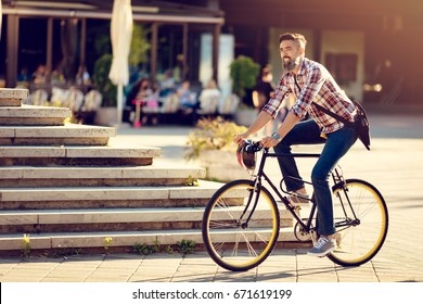 Smiling casual businessman going to work by bicycle.