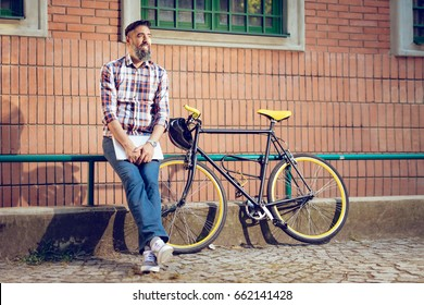 Smiling casual businessman having a break. He is standing in front of the building next to bike and holding laptop.
