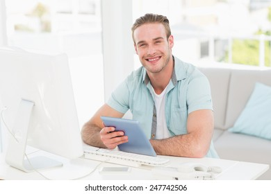 Smiling casual businessman using tablet in his office