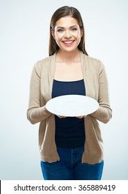 Smiling casual dressed woman hold empty plate. White background isolated.