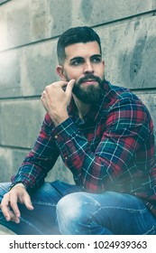 Smiling casual hipster squats leaning on grey wall in the city. Good looking young male model with full beard crouching on street. Modern man on checkers shirt and blue jeans. Urban fashion concept