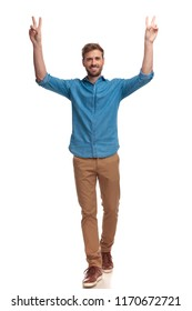 smiling casual man with hands in the air celebrating victory on white background