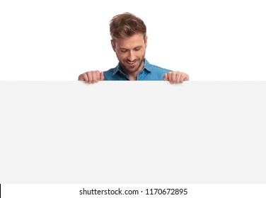 smiling casual man holding blank board looks down at it on white background