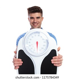 smiling casual man holding and showing a scale on white background