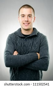 Smiling casual man posing on gray background with arms folded