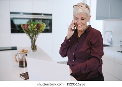 Smiling casual senior woman using laptop while talking on smartphone. Happy mature woman working with a cellphone and laptop at home. Business woman using her mobile phone