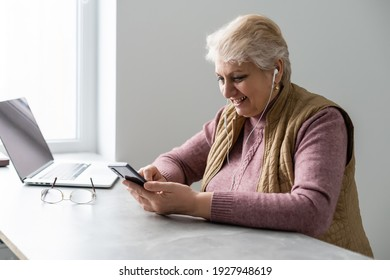 Smiling casual senior woman using laptop while messaging with smartphone. Happy mature woman working with a cellphone and laptop at home and looking at camera. Business woman using her mobile phone