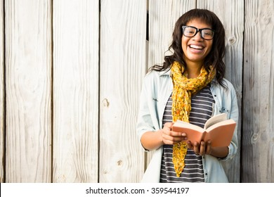 Smiling casual woman reading a book against wooden plank