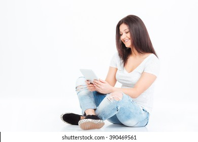 Smiling casual woman sitting on the floor and using tablet computer isolated on a white background
