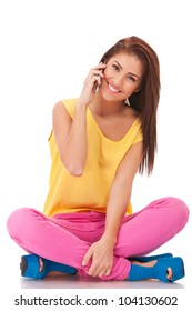 smiling casual woman is sitting and talking on  mobile phone isolated on white