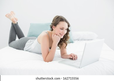 Smiling casual young brunette using laptop while lying in bed at home