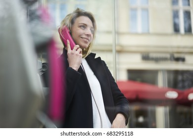 Smiling casually dressed young hipster girl enjoying telephone conversation standing outdoors on city street,female tourist using phone box for making international call standing on blurred background