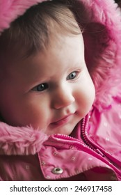 smiling caucasian baby in the pink hood