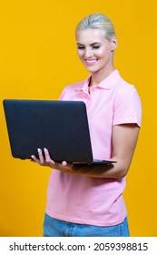 Smiling Caucasian Blond Girl with Laptop Posing With Smile Against Colorful Yellow Background. Vertical Orientation