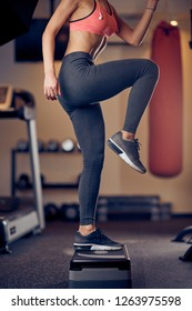 Smiling Caucasian blonde woman with ponytail in sportswear doing exercises on steps . Gym interior, healthy lifestyle concept.