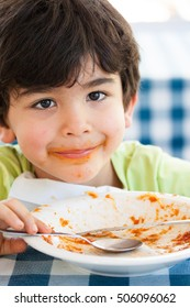 Smiling caucasian boy with empty plate on table