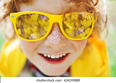 smiling caucasian boy with freckles and curly hair in yellow sunglasses, mirror reflection in glasses is  bokeh with hearts, yellow clothes, red hair