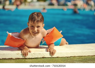 Smiling Caucasian boy getting out from the swimming pool through its side.