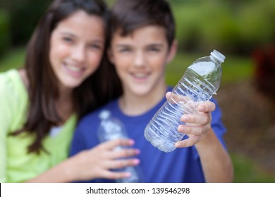 Smiling caucasian boy and girl holding up clear water bottles outside in yard, for recycling, with bottle in focus in foreground