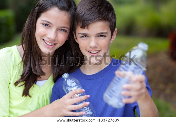 Smiling caucasian boy and girl holding up clear water bottles outside in yard,  for recycling