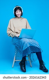 Smiling Caucasian Brunette Girl Sitting with Laptop Posing In Headphones in Hoodie Against Blue Background. Vertical Orientation